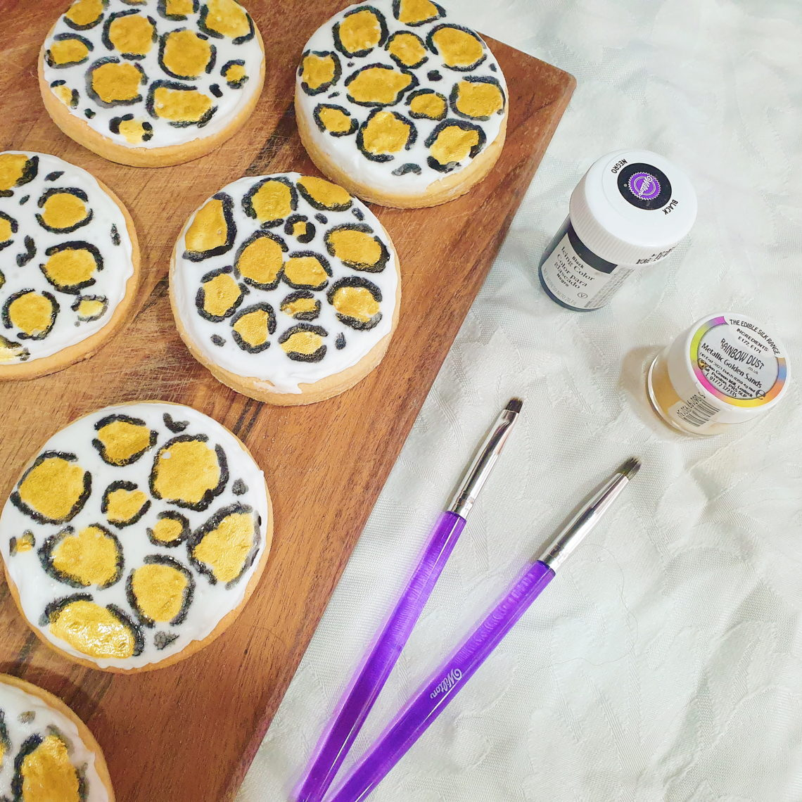 Leopard print cookies on a chopping board, at the side of 2 paint brushes and 2 pots of edible paint