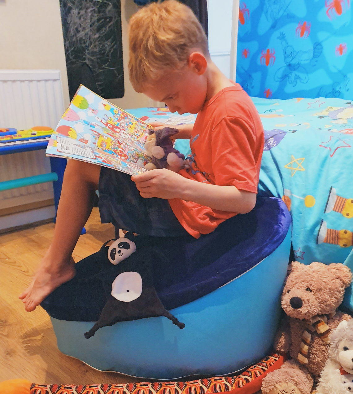 A 6 year old boy in his bedroom sat on a snuggle seat beanbag and reading where's wally
