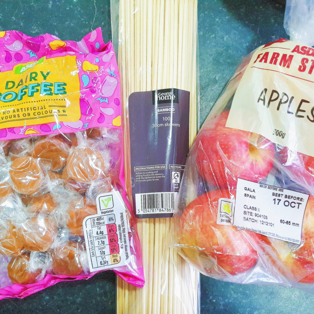 Dairy toffee sweets next to wooden skewers and a bag of apples